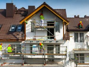 Ouvrier sur échaffaudage qui isole une façade